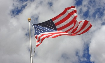 US flag against white clouds and blue sky